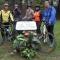 Un gruppo di cicloamatori posa accanto alla targa di Gino Bartali
